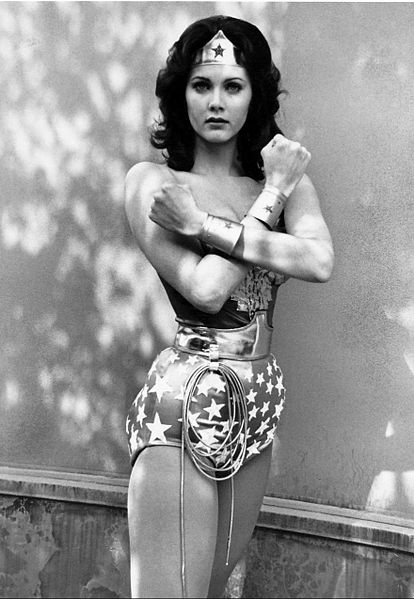 Image depicts a black-and-white image of Lynda Carter as Wonder Woman, using her gauntlets to deflect a bullet.