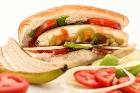 Image depicts a sandwich with a hoagie roll, tomatoes, peppers, onions, and a peeled banana.